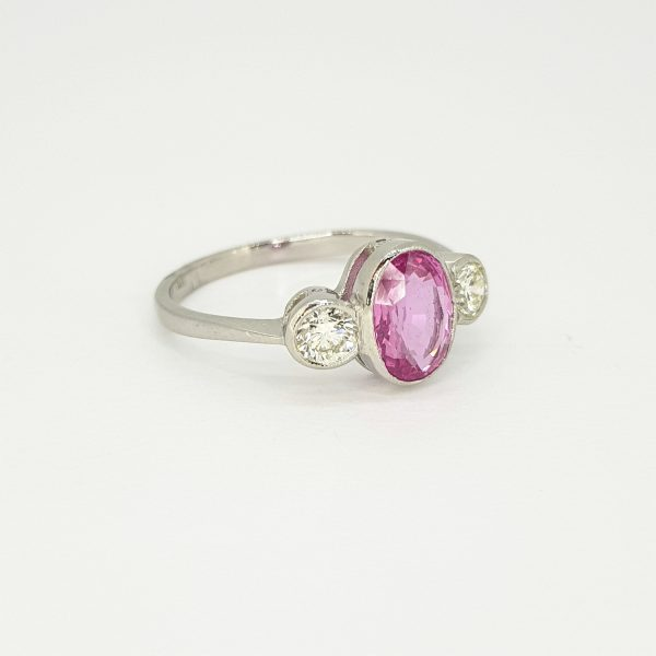 Pink Sapphire and Diamond Three Stone Ring in Platinum; central collet set 1.35ct oval pink sapphire flanked by 0.40cts brilliant cut diamonds