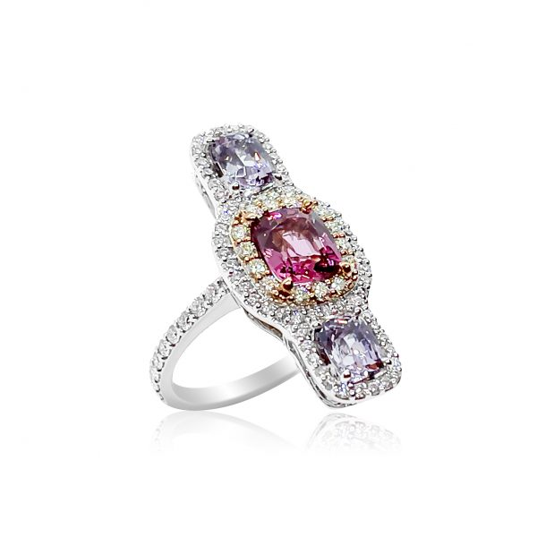 Pink and Lilac Spinel Three Stone Ring with Diamonds; central 1.62ct cushion-shaped pink spinel flanked top and bottom by a cushion-cut lilac spinel, all surrounded by diamonds, in 18ct rose and white gold