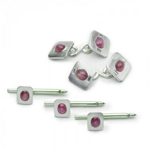 Vintage Tiffany and Co Star Ruby and Platinum Dress Set; comprising a pair of cufflinks and three dress studs, each set with an oval cabochon star ruby with cut corners, cufflinks accented with diamonds, Signed, Circa 1950