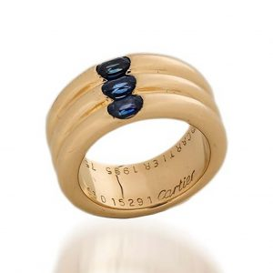 Cartier 18ct Gold Triple Ring Band with Sapphires; 18ct yellow gold triple ring band set with three oval facetted blue sapphires totalling 0.45cts, in original box. Made in France, Paris 1995. Fully hallmarked, signed Cartier and numbered