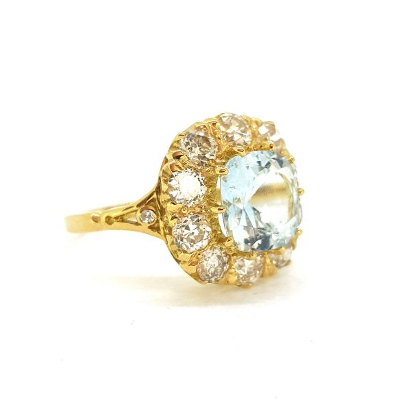Aquamarine and Diamond Cluster Ring; central 2.50ct cushion-shaped aquamarine within a 1.75ct diamond set surround, in 18ct yellow gold