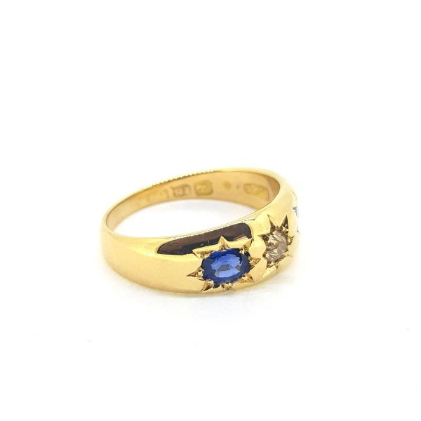 Antique Victorian Sapphire and Diamond Three Stone Ring; central diamond flanked by sapphires, each in star shaped cut down settings in 18ct yellow gold
